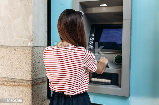 945598452istockphoto A young woman takes money from an ATM. 1130309268