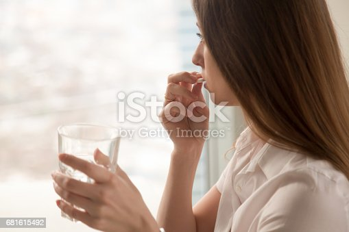 istock Young woman takes pill with glass of water in hand 681615492