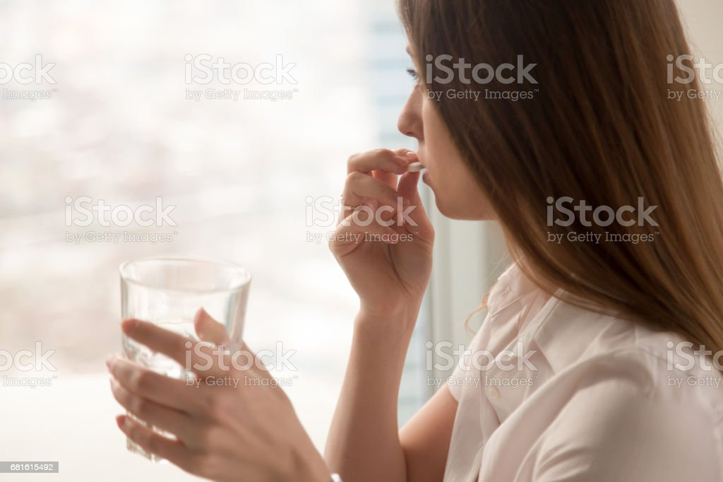Young woman takes pill with glass of water in hand – Foto