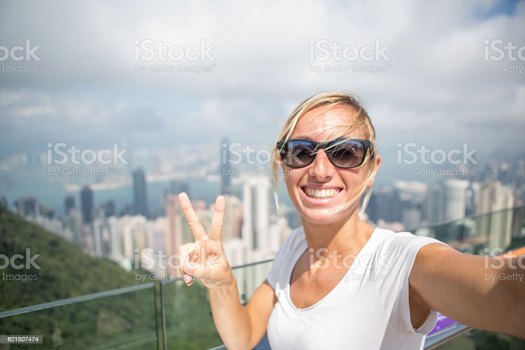 Young woman takes selfie portrait with Hong Kong cityscape foto stock royalty-free