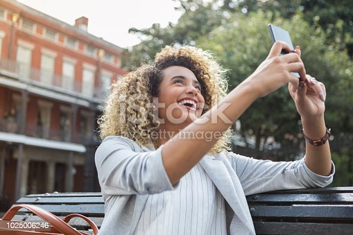 A smiling young woman sits on a park bench.  She holds up a smart phone to take a selfie with a building in the background.