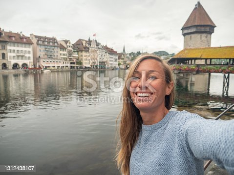 istock Young woman takes selfie with Lucerne city and famous bridge 1312438107