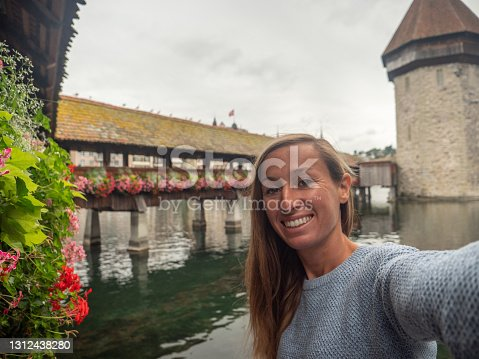 istock Young woman takes selfie with Lucerne city and famous bridge 1312438280