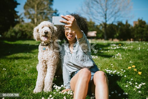 A happy young adult woman enjoys time at a park with her standard poodle.  The take a break from their play to take a self portrait together with her smart phone.