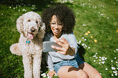 A Young Woman Takes Selfie With Pet Poodle Dog