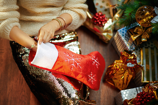 young woman takes something out of red Christmas stocking