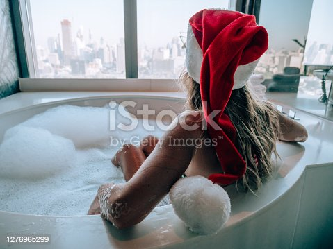 istock Young woman taking a bath wearing Santa hat, Christmas relaxation 1276965299