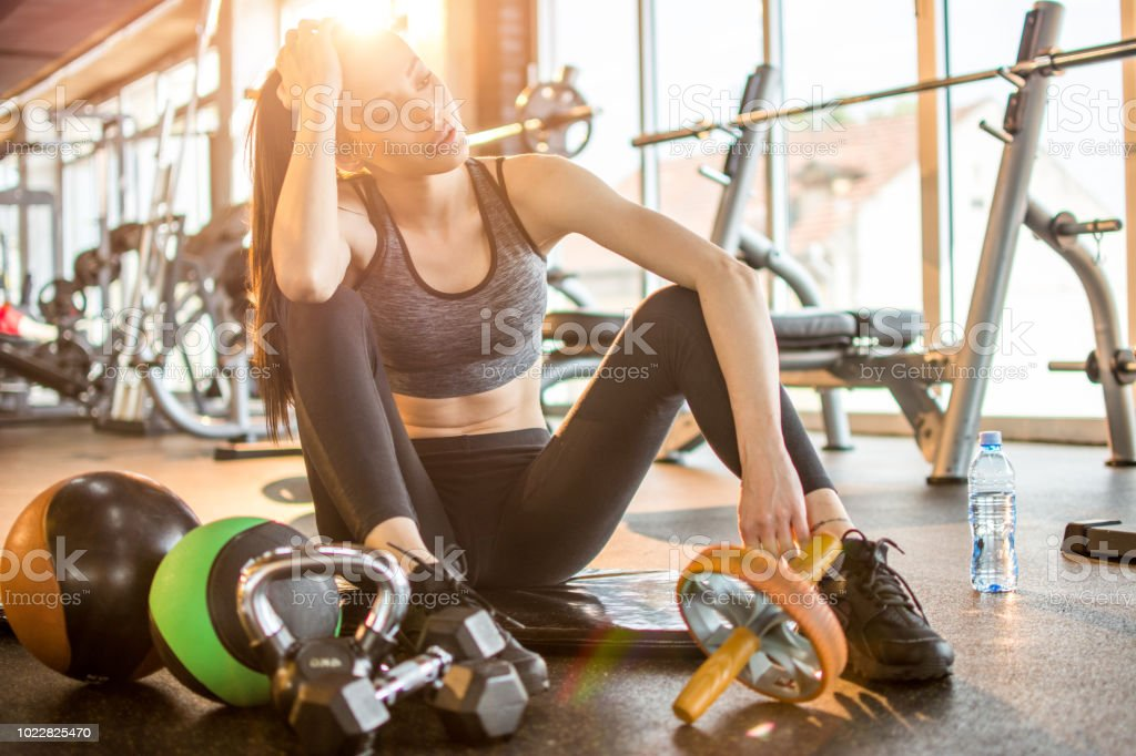 Young woman taking a break and sitting on the exercise mat in gym stock photo