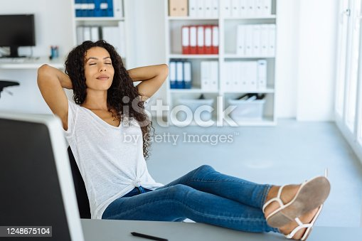 Young woman taking a break at the office sitting back with her feet on the desk and eyes closed relaxing