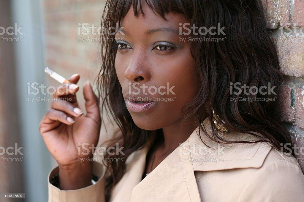 Young woman taking a cigarette break stock photo