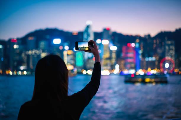 junge frau, die ein foto von victoria harbour nachtansicht - reiseblogger stock-fotos und bilder