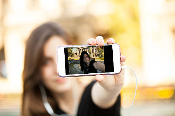 young  woman taking a photo with her phone - beautiful college girl pics stock photos and pictures