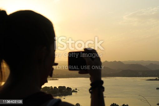 599114758 istock photo Young woman taking a picture of the beautiful sunset in Udaipur 1136403105