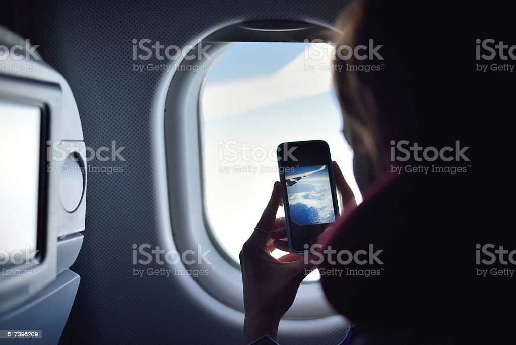 Young woman taking a picture on an airplane stock photo