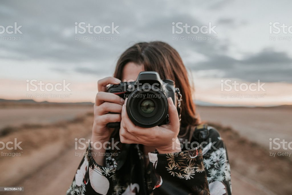 Young woman taking a picture A young woman using a DSLR camera Adult Stock Photo