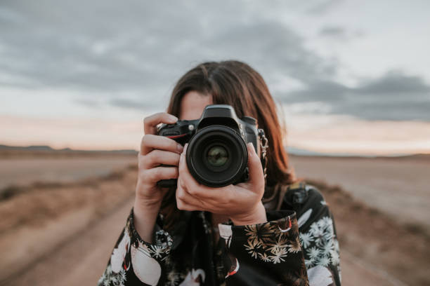 young woman taking a picture - camera photographic equipment stock photos and pictures