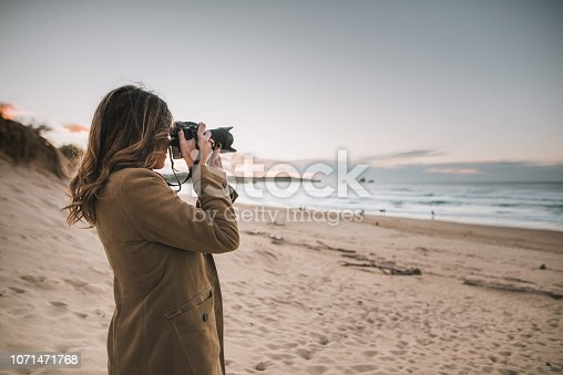 Young woman taking a picture with a modern DSLR camera