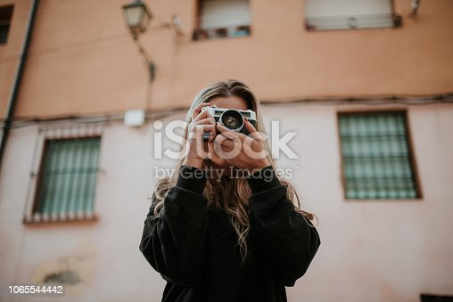 A young woman taking a picture with a vintage camera
