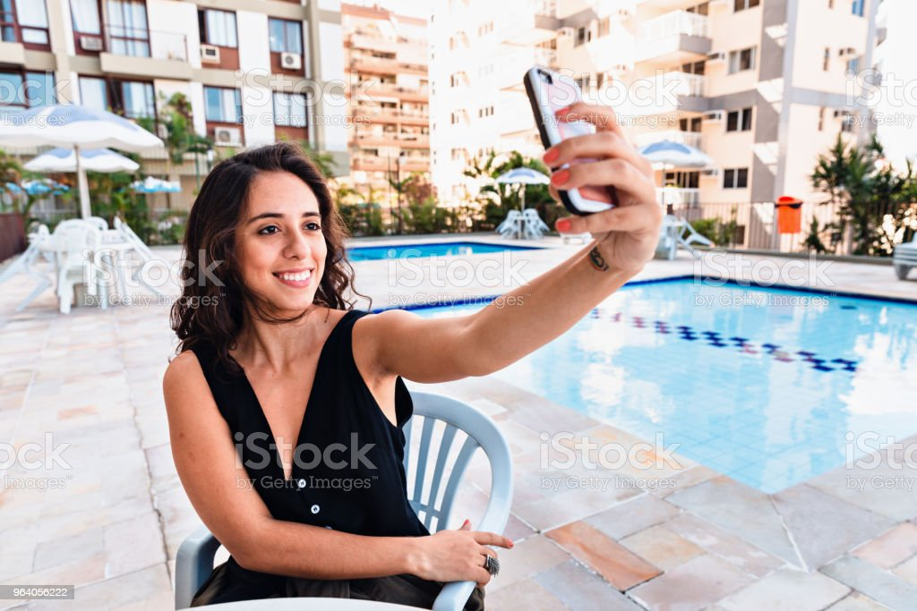 Young woman taking a selfie by the pool - Royalty-free Adult Stock Photo