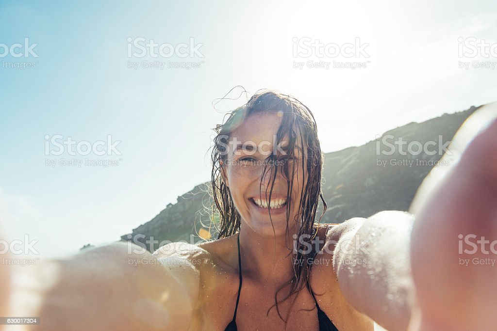 young woman taking a POV Selfie photograph on Porthcurno beach. stock photo