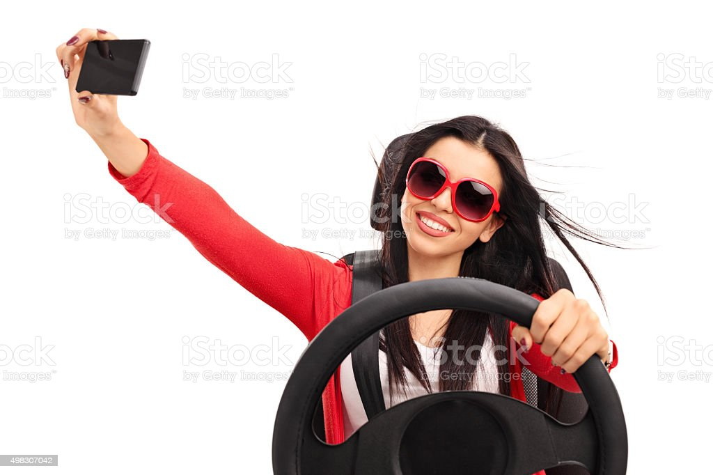 Young woman taking a selfie while driving a car stock photo