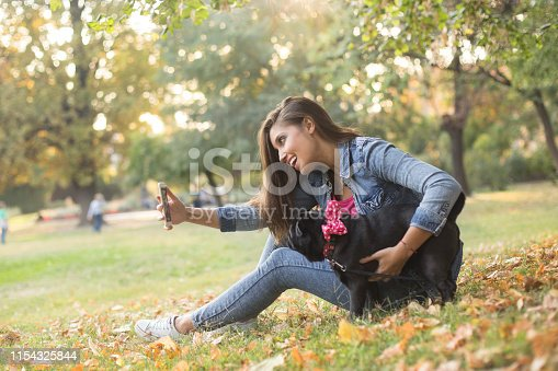 istock Young woman taking a selfie with her pug 1154325844