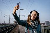 istock Young woman taking a selfie with her smart phone on a railway bridge 1308605083