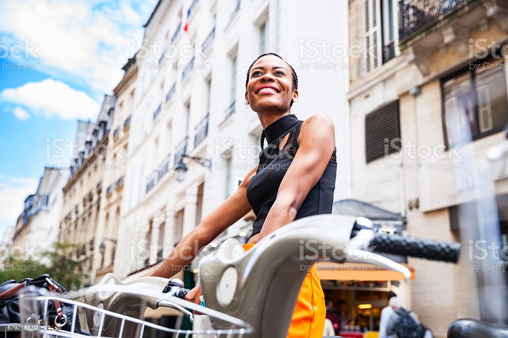 Young woman taking a shared bicycle in Paris stock photo