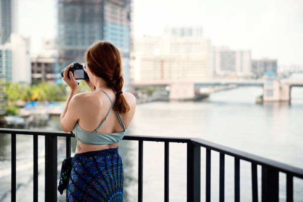 Young woman taking a video on a balcony in vacations. stock photo