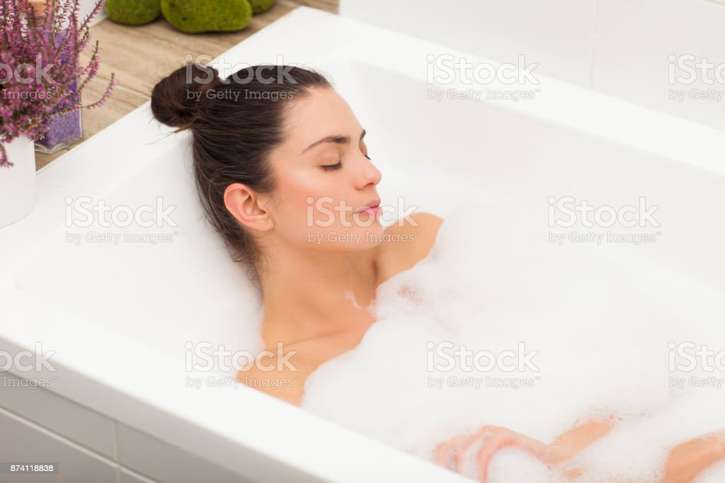 Young woman taking bath full of foam. - foto stock