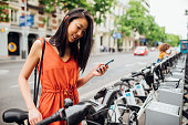 Young cheerful woman taking bicycle out from bicycle rack on the street with smartphone in her hand
