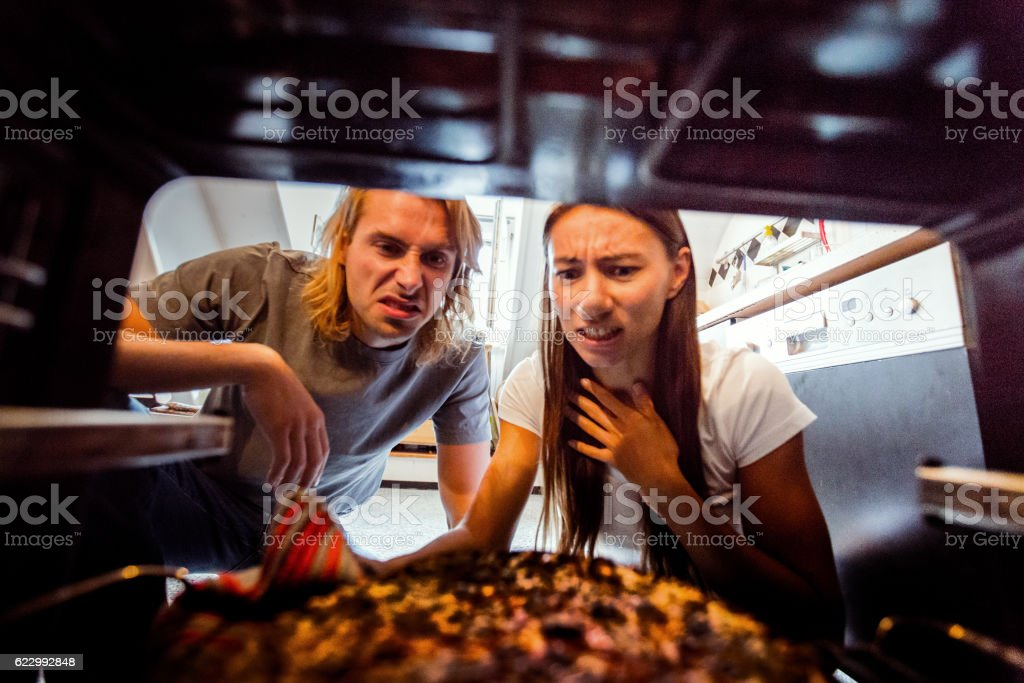 Young woman taking burnt pizza from stove stock photo