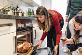 young woman taking christmas poultry out of oven