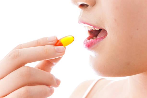 若い女性は、薬を飲んで ストックフォト
