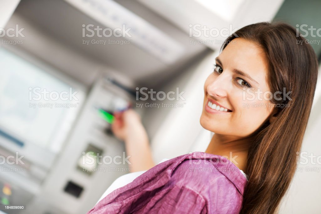 Young woman taking money from ATM. royalty-free stock photo
