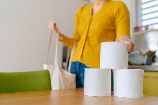 A young woman is taking out toilet papers from a reusable  shopping bag at home.