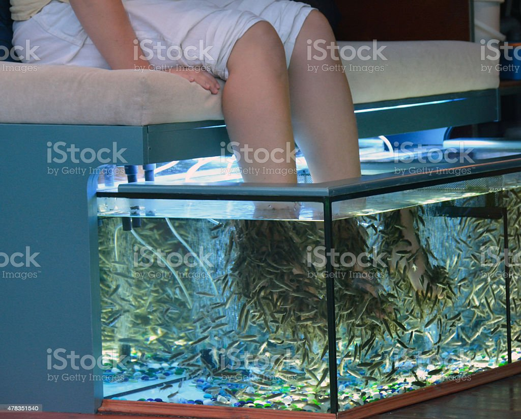 Young woman taking pedicure procedure in the aquarium stock photo