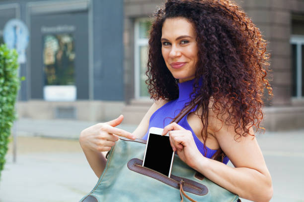 Young woman taking phone out of her purse stock photo