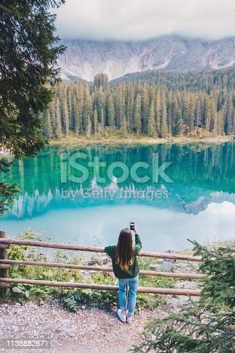 Woman taking a photo on a mobile phone at Karersee / Lago di Carezza lake in Dolomites, Italy