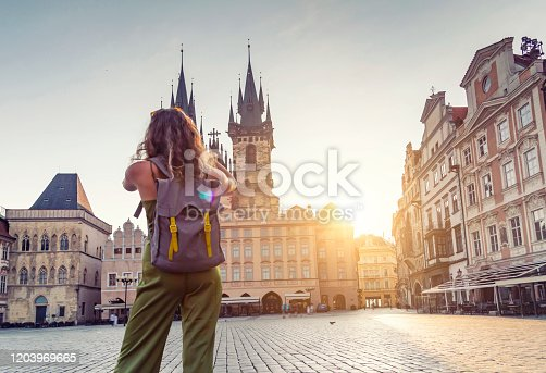 Young woman taking photo from the Tyn Church in Prague