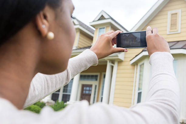 Young woman taking photo of new home with smart phone stock photo