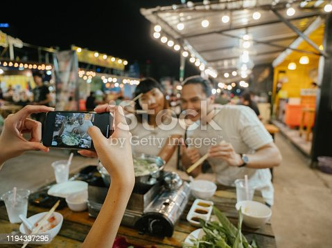 Happy asian friends taking selfie and cheering and toasting with traditional food at dinner outdoor in flea market. Bangkok, Thailand.