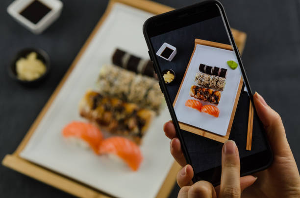 junge frau nehmen foto sushi platte smartphone. - sushi essen stock-fotos und bilder