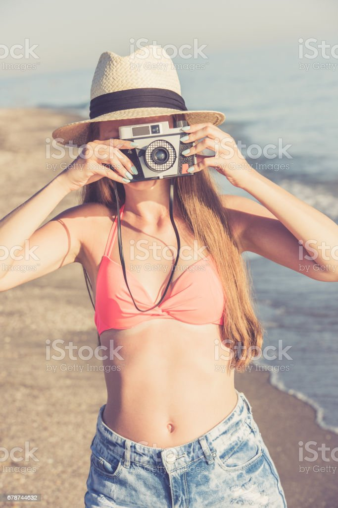 Young woman taking photo on the beach using retro camera royalty-free stock photo