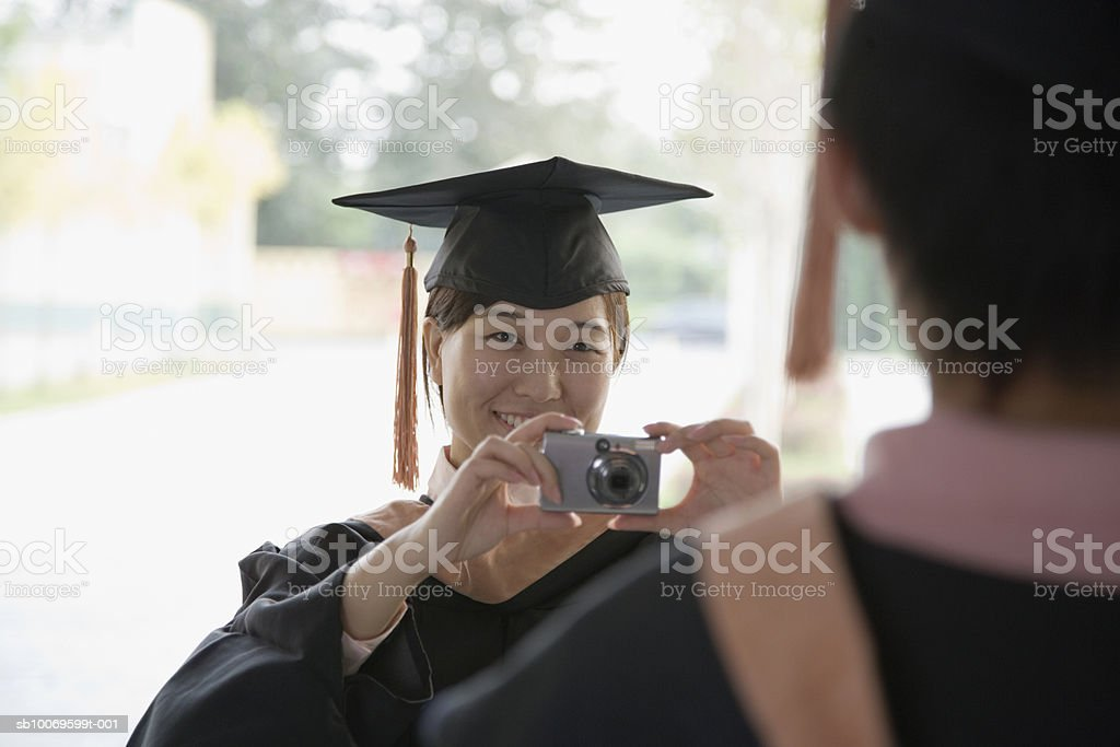 Young woman taking photograph of friend in graduation gown with digital camera foto stock royalty-free