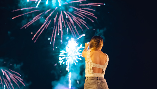 Young woman admiring and photographing firework display