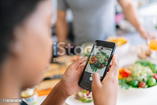 A young woman is taking photos of salad with her smart phone.