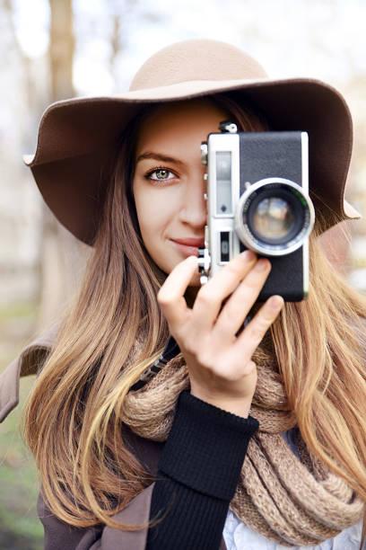 Mujer joven tomando fotos con la cámara retro - foto de stock