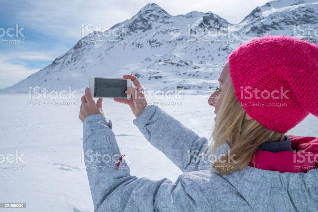 Young woman taking picture of frozen lake stock photo