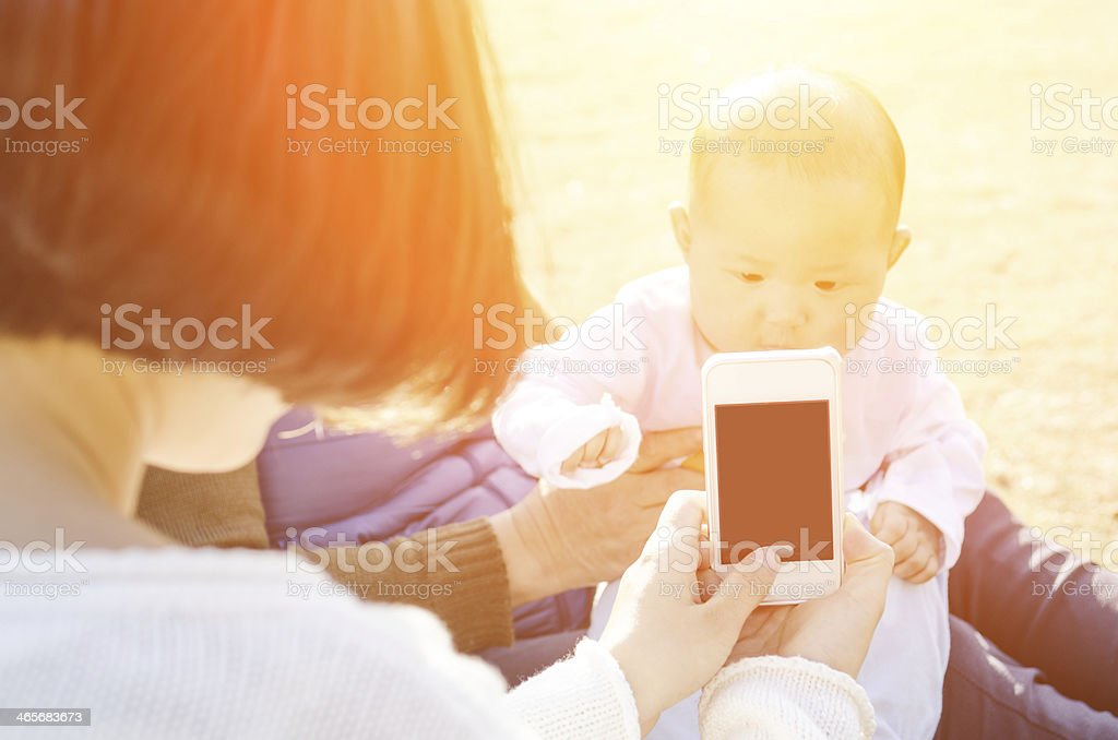 young woman taking picture of her son with smartphone stock photo